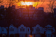 Lens flare from setting sun between layers of cloud over inner-city south London rooftops. As the sun sinks inn the winter sky, over the inner-city of Britain's capital, we see a variety of eras in the architecture of urban housing: From Ewardian period in the foreground to the tower blocks from the 60s in the distance. A warm glow of light flares from the camera lens to give an almost cosy feel to the landscape while giving a sense of raw cold on this April evening.