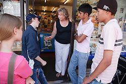 Shop keeper talking to teenage group.