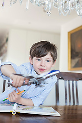 Portrait of boy playing with model airplane, smiling