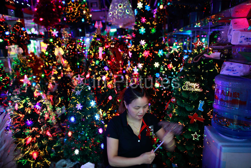 A woman sits in her stall selling plastic Christmas trees at the Yiwu International Trade City in Yiwu, Zhejiang Province, China on Sunday, 11 September 2011.   As the trading hub for small and medium manufacturers and exporters in the Yangtze River Delta region, Yiwu faces an uncertain future as export orders decline due to the slow economic recoveries of China's two largest trading partners, Europe and the United States