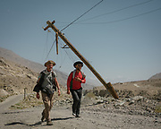 Paul Salopek walking with Firuz next to decaying soviet electrical poles. <br /> Trekking between Darshai and Namadgut village.<br /> Sights and places to see while walking along the Tajikistan side of the Wakhan Corridor.