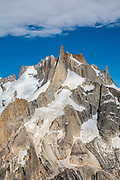 """Paso Quadrado affords a great view south to the rock pillar of Aguja Pollone, near El Chalten, Argentina, Patagonia, South America. We hiked scenic Rio Electrico Valley to Refugio Piedra del Fraile (""""Stone of the Friar"""", 14.5 km round trip) to stay overnight in dorms. A path from the refuge ascends very steeply to Paso Quadrado (gaining 1340 m vertically in 8.4 km round trip). The last kilometer climbs up steep snow which could require crampons if icy (but was passable in soft snow using our trailrunning shoes). Views keep improving as you ascend."""