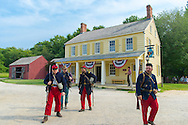 """Old Bethpage, New York, USA. August 30, 2015. American Civil War soldiers from the 14th Brooklyn Regiment (14th New York State Militia) AKA The Brooklyn Chasseurs, are portrayed in front of the yellow and white Noon Inn tavern during the Old Time Music Weekend at the Old Bethpage Village Restoration. During their historical reenactments, members of the non-profit 14th Brooklyn Company E wear accurate reproductions of """"The """"Red Legged Devils"""" original Union army uniform."""