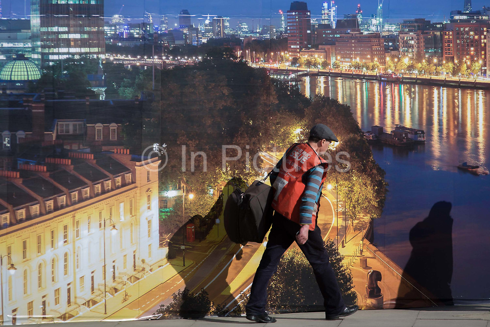 A Big Issue seller walks past a property company's construction hoarding, a night time panorama of  Thames riverside properties. The temporary hoarding will stay in place for the time that the company's new residential riverfront apartments are under construction. In the image, the river Thames bends round to Westminster as the man walks past. The Big Issue is a small-budget magazine started in 1991 by Gordon Roddick and A. John Bird in response to the growing number of rough sleepers on the streets of London. The two believed that the key to solving the problem of homelessness lay in helping people to help themselves. Vendors buy their magazines with their own money and sell them at their own profit or loss.