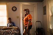 MONTGOMERY, AL – JUNE 11, 2019: Myra Powell (right) stands in the apartment she rents with her fiancé, Stefvenie Buckner, in the Capitol Heights neighborhood. At age 19, while 26 weeks pregnant, Powell suffered a catastrophic placental abruption and was taken by ambulance to a nearby hospital. While there, doctors discovered her placenta had fully detached from the uterine wall, depriving her twin boys of oxygen. Silas and Stefvon died in utero. Narrowly escaping death herself, Powell would later be diagnosed with HELLP syndrome, a pregnancy-induced blood pressure condition in the eclampsia family that kills nearly a third of all women who develop it. As a young, poor, black woman from the south, Powell represents the deadliest cross-section of demographics among mothers in America, where more women die from pregnancy related causes than any other wealthy country in the world.