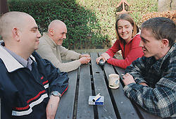 Group of male residents of homeless hostel for people with learning difficulties sitting outside on garden bench talking with assistant manager,