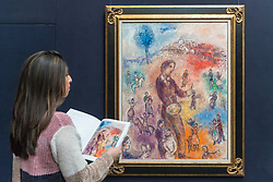 "© Licensed to London News Pictures. 20/02/2019. LONDON, UK. A staff member views ""Le peintre à la fête"", 1982, by Marc Chagall (Est. £1.0-1.5m).  Preview of Sotheby's Impressionist & Modern and Surrealist Art sales.  The auction will take place at Sotheby's New Bond Street on 26 February 2019.  Photo credit: Stephen Chung/LNP"