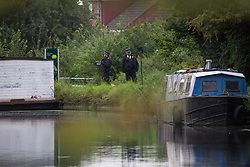© Licensed to London News Pictures.  26/08/2021. London, UK. Police guard a canal barge in the vicinity of Ferrymead Avenue, Ealing in west London. Yesterday before 6pm, officers found 49-year-old Lee Peacock on the boat -  wanted in connection to the murder of two people in Westminster on Thursday, 19 August. The man has sustained serious injuries, which at this stage it is believed were self-inflicted. The man has been transported to hospital where his condition is believed to be life threatening. Photo credit: Marcin Nowak/LNP