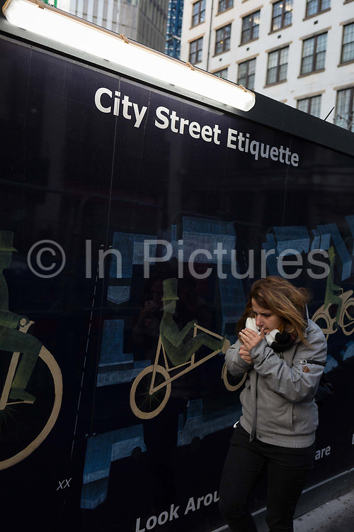City dwellers pass beneath advice about street etiquette on a construction hoarding in the City of London, the capitals financial district, on 24th January 2019, in London, England.