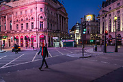 A young man crosses the road in an almost deserted Picadilly Circus in London on March 27th, 2020. The centre of London is extremely quiet with almost every business closed and very few people about because of the Governments lockdown measures due to the Coronavirus crisis.