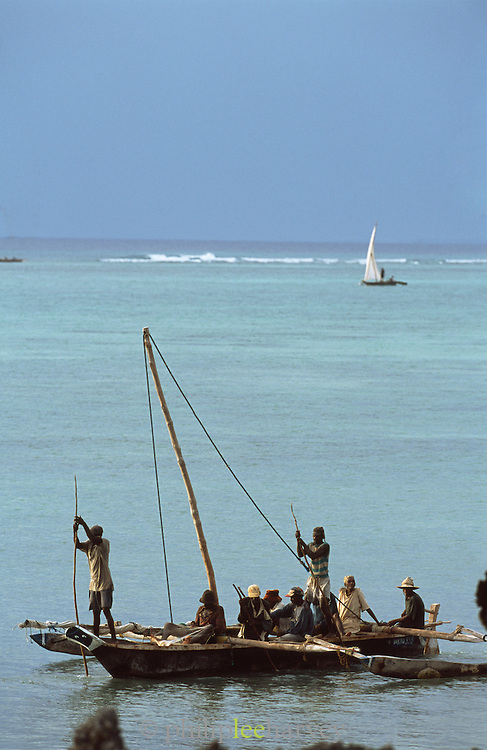 Fishermen on a traditional dhow boat in the water off the island of Zanzibar, a semi autonomous region of Tanzania