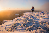 Female hiker at sunrise on winter summit of Pen Y Fan, Brecon Beacons national park, Wales