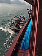 Vietnam, Ha Long Bay: approaching the boat to sell fish .