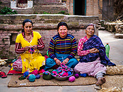 15 MARCH 2017 - BUNGAMATI, NEPAL:  Women sew tourist nick-nacks in front of an earthquake damaged home in Bungamati. They were making mittens and hats which will be sold in the tourist markets of Kathmandu. Recovery seems to have barely begun nearly two years after the earthquake of 25 April 2015 that devastated Nepal. In some villages in the Kathmandu valley workers are working by hand to remove ruble and dig out destroyed buildings. About 9,000 people were killed and another 22,000 injured by the earthquake. The epicenter of the earthquake was east of the Gorka district.             PHOTO BY JACK KURTZ