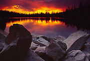 Idaho. North 20 Mile Lake near McCall. Sunset with forest trees reflecting in water.
