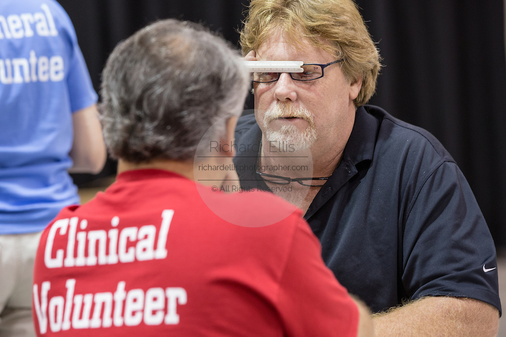 A patient has his eyes check and eyeglasses measured by a volunteer during a free medical mission held by the SC Hospital Association on August 23, 2013 in North Charleston, South Carolina. More than 1,000 people showed up to receive free dental and medical care.