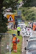 Police officers lead away an anti-HS2 activist with a banner who had occupied a mature oak tree in order to try to prevent or delay tree felling alongside the Fosse Way in connection with the HS2 high-speed rail link on 24th August 2020 in Offchurch, United Kingdom. The controversial HS2 infrastructure project is currently expected to cost £106bn and will destroy or significantly impact many irreplaceable natural habitats, including 108 ancient woodlands.