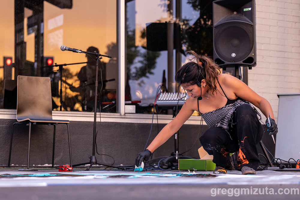 Multimedia Iraqi-American artist Luma Jasim collaborates with musician Ryan Garrett to produce a performance that combines improvised live large-scale painting and music at LED's Art on the Block series in Boise, Idaho on September 2, 2021.