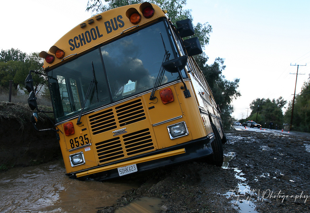 A school bus teeters on the edge of a wash after being swept off Temescal Canyon Rd, by a flash flood Tuesday afternoon. The bus was carrying around 20+ students when the incident occurred, but no one was injured.