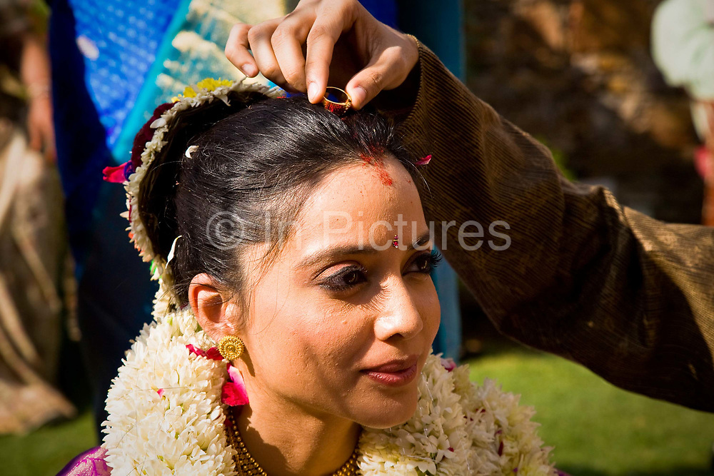 At a Hindu wedding ceremony, bride Shweta Singhal has groom Rohit dip his wedding ring into  a red powder known as sindoor and marks  his newly wed wife forehead as a sign of their marriage, they are surrounded vy most of their most immediate families, Neemrana Fort Palace, Rajasthan, India.
