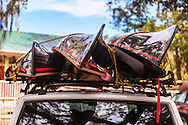 End-on view of three small, black canoes strapped to the roof of a car. WATERMARKS WILL NOT APPEAR ON PRINTS OR LICENSED IMAGES.