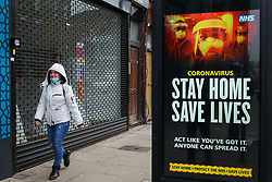 © Licensed to London News Pictures. 15/01/2021. London, UK. A woman wearing a protective face covering walks past the Government's ''Stay Home, Save Lives' Covid-19 publicity campaign poster in north London as research shows that the capital's R rate is below 1. The research from Cambridge University suggests that the rate of transmission might be slowing down in London and the South East, where the mutant variant of the SARS-Cov-2 virus first began spreading. Photo credit: Dinendra Haria/LNP