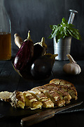 Baked eggplant on piece of slate with raw eggplant basil garlic and olive oil in the background.