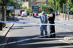 © Licensed to London News Pictures. 01/06/2019. London, UK. A forensic officer speaking with a police officer on Seven Sisters Road, near the junction of Vartry Road in Haringey, north London, where a man in his 30s was found suffering from a stab wound to his leg. Police were called by London Ambulance Service just after 3am on Saturday, 1 June 2019. The victims condition in unknown.  Photo credit: Dinendra Haria/LNP