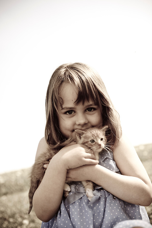 Girl 4-6 years smiling hugging kitten and looking into camera sepia