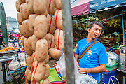 "03 OCTOBER 2012 - BANGKOK, THAILAND:    A sausage vendor in Khlong Toey Market in Bangkok. Khlong Toey (also called Khlong Toei) Market is one of the largest ""wet markets"" in Thailand. Thousands of people shop in the sprawling market for fresh fruits and vegetables as well meat, fish and poultry every day.        PHOTO BY JACK KURTZ"