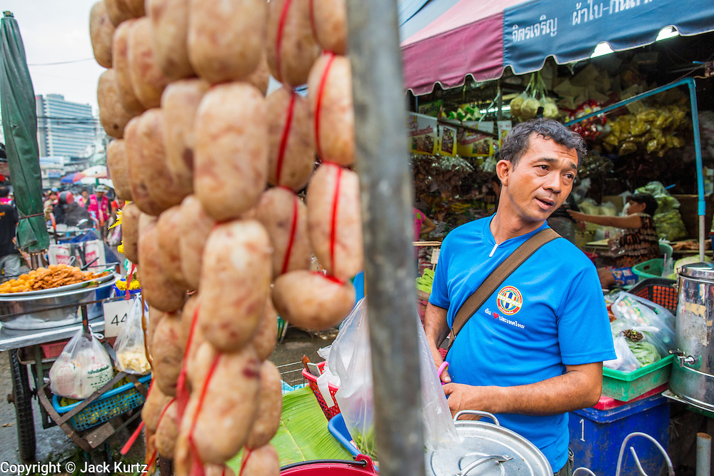 """03 OCTOBER 2012 - BANGKOK, THAILAND:    A sausage vendor in Khlong Toey Market in Bangkok. Khlong Toey (also called Khlong Toei) Market is one of the largest """"wet markets"""" in Thailand. Thousands of people shop in the sprawling market for fresh fruits and vegetables as well meat, fish and poultry every day.        PHOTO BY JACK KURTZ"""