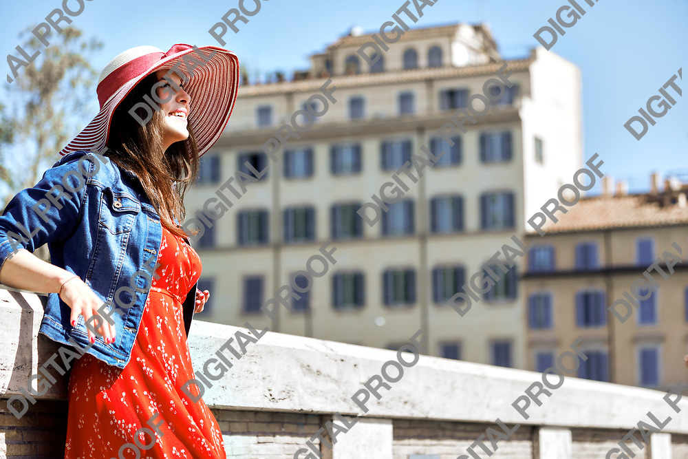 Smiling tourist woman in hat leaning on handrail and looking away on sunny town street.