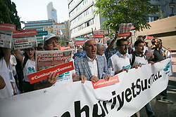"""Journalists and people hold a banner reading """"Cumhuriyet won't be silenced"""" and copies of Cumhuriyet opposition daily reading """"We want Justice"""" as they march to the courthouse from Cumhuriyet daily's headquarters on July 24, 2017 in Istanbul, Turkey. Photo by Tolga Sezgin/NARphotos/ABACAPRESS.COM"""