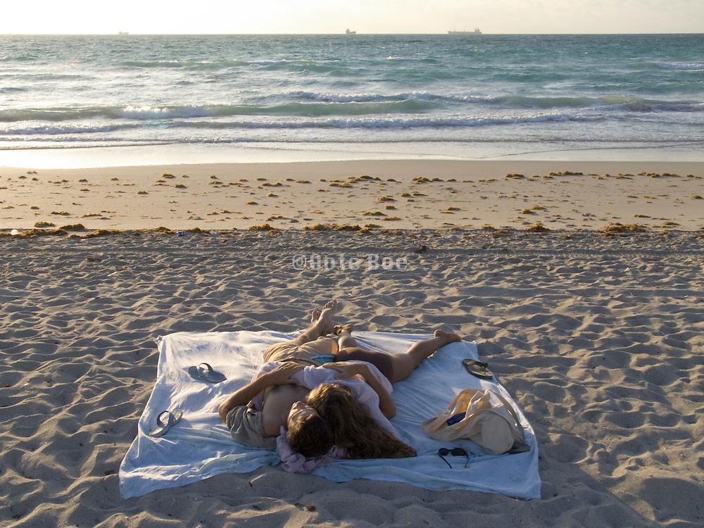 young couple sleeping on the beach Miami USA