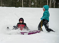 """Giovanni and Sincere enjoy their """"snow day"""" sledding at Memorial Park in Laconia Tuesday morning.  (Karen Bobotas Photo/for The Laconia Daily Sun)"""