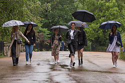 © Licensed to London News Pictures.  18/06/2021. London, UK. A group of friends walk in the rain through Hyde Park, central London. Weather forecasts predict heavy rains in upcoming days. Photo credit: Marcin Nowak/LNP