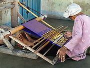Sitting on the floor, an elderly Hindu Cham woman weaves a priest's turban with cotton and silk threads on a back-strap loom outside her home in My Nghiep village, Ninh Thuan province, Central Vietnam. The Cham people are remnants of the Kingdom of Champa (7th to 18th centuries) and are recognised by the government as one of Vietnam's 54 ethnic groups.