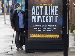 © Licensed to London News Pictures. 02/02/2021. London, UK. A member of the public stands next to a Covid-19 information sign in the high risk area of Hanwell, West London where the South African mutation has spread. Yesterday, two people tested positive in Woking, Surrey for the South African variant by community transmission with no links to South Africa as 80,000 people in the South East will be offered urgent Covid-19 tests.  Earlier, Health Minister Matt Hancock urged residents in high risk areas to take extra special precautions . Photo credit: Alex Lentati/LNP