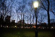 a street light with high rises in the back ground Central park in New York City
