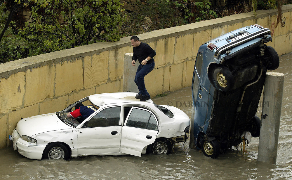 Two unidentified men retrieve a friend's possessions from his car after it was swept away by flood waters in the town of Birkirkara, outside Valletta, November 6, 2002.  Heavy rainfall caused widespread flooding and damage throughout the Maltese islands, though no serious injuries were reported...MALTA OUT..REUTERS/Darrin Zammit Lupi