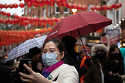 People wearing face masks for Chinese new year celebrations in Chinatown on 26th January 2020 in London, England, United Kingdom. Due to the recent coronavirus outbreak an increased number of Chinese / Asian and western people are wearing face masks in public despite NHS Englands advice that the risk of getting the illness in the UK is low. Wuhan novel coronavirus WN-CoV is a new respiratory illness that has not previously been seen in humans. Each year local Chinese community and Londoners gather on this famous area of central London which is the focus of celebrations for this, the Chinese Year of the Rat. Bright red lanterns are strung across between the buildings creating a canopy of colour.