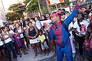 Man in Spiderman costume talking to crowd with a megaphone. Protest in Copacabana, Rio de Janiero, in response to the mysterious death of professional dancer Douglas Rafael da Silva Pereira, allegedly at the hands of the Police. The favela Pavao-Pavaozinho that sits in between Copacabana and Ipanema. These protests saw a rare solidarity between the mostly middle class black bloc movement and members of the favela community.