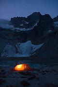 A tent glows at twilight besides Luna Lake, Northern Picket Range, North Cascades National Park, Washington.