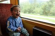 Zillertal, Tyrol, Austria, Steam hauled tourist train on the narrow gauge Zillertalbahn Car interior. Excited boy sits by the window