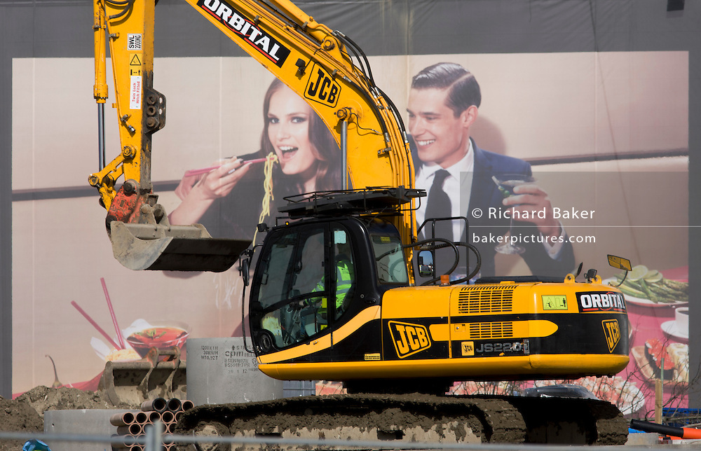 JCB excavator and aspirational poster on wall during building of 2012 Olympic Westfield City shopping centre, Stratford.