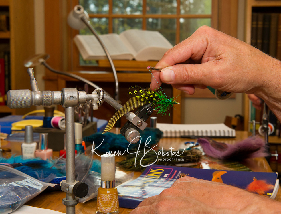 Dan Tarullo of Alton delicately attaches dyed bird feathers and dyed deer tail to a fish hook during Gilford Public Library's Fly Tying class Thursday evening.  (Karen Bobotas/for the Laconia Daily Sun)
