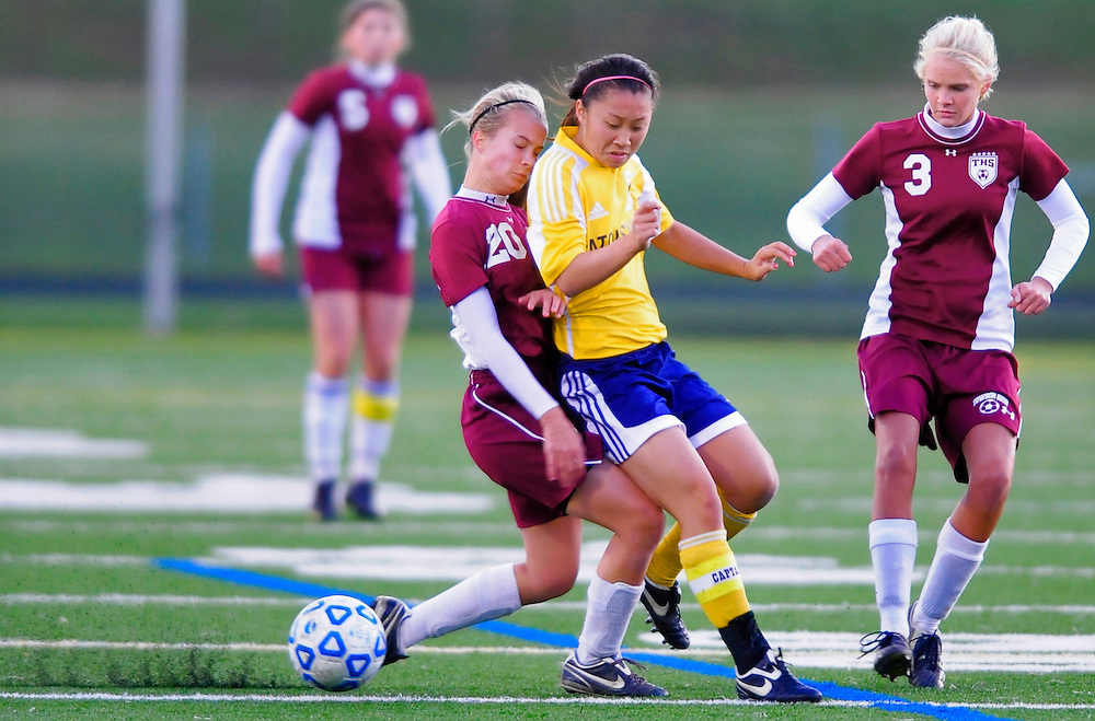 (staff photo by Matt Roth)..Towson defender Mo Sunderland, left, and Catonsville midfielder Danielle Pulliam, middle, almost bring Towson's Julia Bader into their collision. Catonsville shut out guest Towson 3-0 in 3A North Region soccer semifinal play Friday, November 6, 2009.