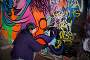 Female graffiti artist spray painting a wall at the Southbank, London. This area is popular for street arts.