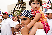 10 APRIL 2006 - PHOENIX, AZ: A man carries his daughter through downtown Phoenix during a demonstration and march for immigrants rights. More than 200,000 people participated in a march for immigrants's rights in Phoenix Monday. The march was a part of a national day of action on behalf of undocumented immigrants. There were more than 100 such demonstrations across the US Monday. Protestors were encouraged to wear white, to symbolize peace, and wave American flags, to demonstrate their patriotism to the US.  Photo by Jack Kurtz