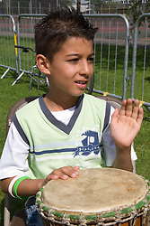 Young boy taking part in a drumming workshop at a Parklife summer activities event,